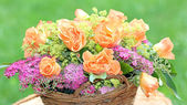 Flower basket with roses and spiraea in the garden — Stock Photo