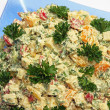 Dressed Emmenthal cheese salad with parsley on a glass plate — Stock Photo #22443829