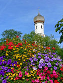 Bavarian church and big colorful flower pot full bloom — Stock Photo