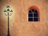 Mediterranean house facade with glooming lantern and arched window — Stock Photo