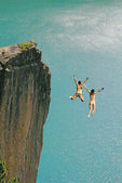 Two cliff jumping girls, against turquoise ocean — Stock Photo