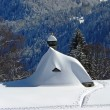 Snowbound chapel in the austrian alps - Stock Photo