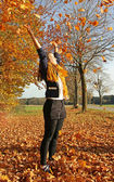 Teenage girl throwing autumn leaves — Stockfoto