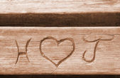 Initials of a love couple, carved in a bench plank — Stock Photo