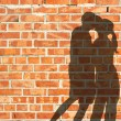 Kissing silhouette couple against red brick wall — Stock Photo