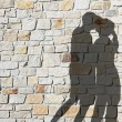 Silhouette of kissing couple, against natural stone wall — Stock Photo