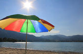 Lake-shore of tegernsee with sunshade in rainbow colors — Stock Photo