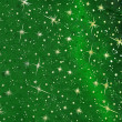 Green christmas background with golden glittering stars — Stock Photo