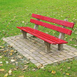 Red bench on pavement in the park — Stock Photo