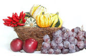 Wicker basket with gourd pumpkins, blue grapes, apples and chili — Stock Photo