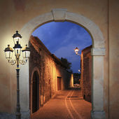 Moody illuminated alleyway with arched gate and burning lantern — Stock Photo