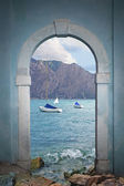 View through arched door to lake and mountains — Stock Photo