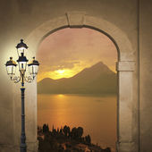 Arched door with view to sunset landscape, romantic mood with burning lantern — Stock Photo