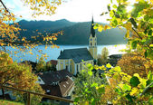 Autumnal view through branches to schliersee lake and church — Stock Photo