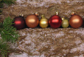 Christmas baubles on firewood logs with snowflakes and fir branc — Stock Photo