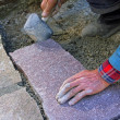 Senior landscape gardener fitting a flagstone tile with a rubber — Stock Photo