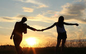 Teenage sisters, holding hands - sunset silhouettes — 图库照片