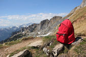 Red knapsack, against austrian mountain panorama — Stock Photo