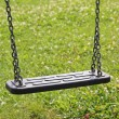 Children swing, against green grass, childrens playground — Stock Photo #39100313