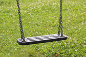 Children swing, against green grass, childrens playground — Stock Photo