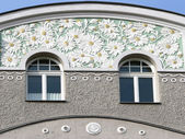 Historic stucco facade with windows and ornamental flower patter — 图库照片