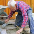 Aged senior, paving a patio, professional precision work — Stock Photo