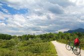 Isar sulak, dramatik bulutlu gökyüzü ile yalnız b binicilik bisiklet — Stok fotoğraf