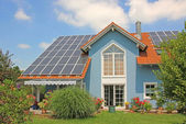 Modern new built house and garden, rooftop with solar cells, blu — Stock Photo
