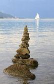 Stone pile at lake tegernsee, sailboat — Stock Photo