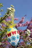 Easter egg with paper flowers, hanging in a shrub — Stock Photo
