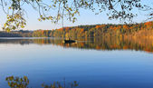Tranquil lake with lonely rowing boat  — Stock Photo