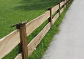 Wooden fence and green meadow, diagonally — Stock Photo