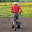 Man flattening the soil for preparing garden lawn — Stock Photo