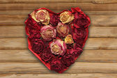 Love heart with dried rose buds, rustic style — Stock Photo