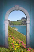 View through arched door - alpine lake and mountains — Stock Photo