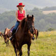 Woman in red hat riding — Stock Photo