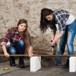 Two long-haired young woman with an angle grinder — Stock Photo #42725951