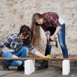 Two long-haired young woman with an angle grinder — Stock Photo #42726303
