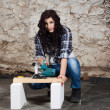 Young long-haired woman with a circular saw — Stock Photo