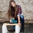 Young long-haired woman with a circular saw — Stock Photo #42727599