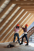 Two young woman repairing the roof of the house — Stock Photo