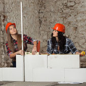 Two young long-haired woman built a new wall from blocks — Stock Photo