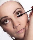 Painting of women eyelashes using mascara — Stock Photo