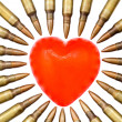 A heart shaped bar of soap is surrounded by 5.56 cartridges - Stock Photo