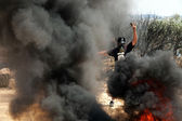 Palestinian Protester with Slingshot Amidst Smoke — Stock Photo