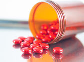 Coated red tablet and brown bottle on dispensing tray — Stock Photo