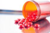 Gecoate rode tablet en bruine fles op de verstrekking van lade — Stockfoto