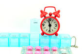 Weekly pill box and red clock on white blackground — Stock Photo