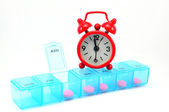 Dialy pill box and red clock on white blackground — Stock Photo