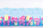 Closed up capsule and tablets in daily pill box — Stock Photo